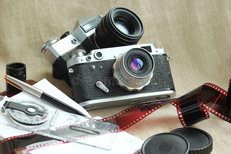 Het reuze openlucht opgeblazen decorClassic stilleven van sneeuwmankerstmis met retro camera's, films, notitieboekjes, kompas en  royalty-vrije stock foto
