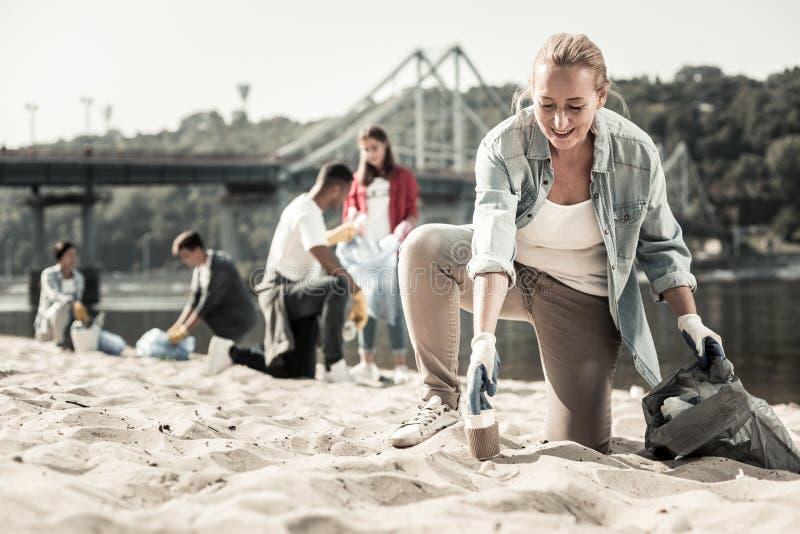 Het richten van blonde-haired vrouw die denimoverhemd dragen die zich dichtbij de rivier aanmelden stock afbeelding