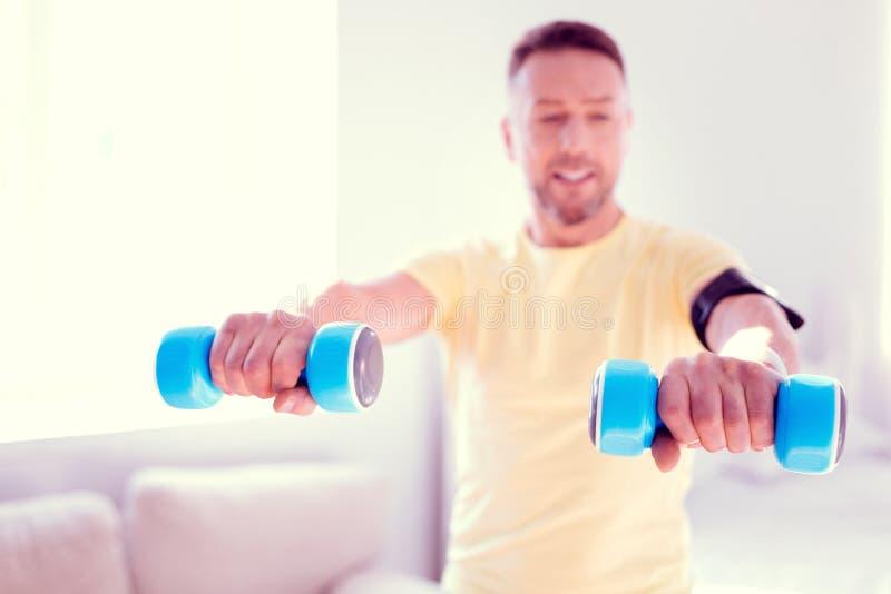 Het richten van de gebaarde mens die gezonde levensstijl leidt die tot blauwe handgewichten houdt royalty-vrije stock foto's