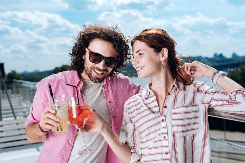 Het richten van glimlachende vrouw die haar glas met de haar mens klinken stock foto's