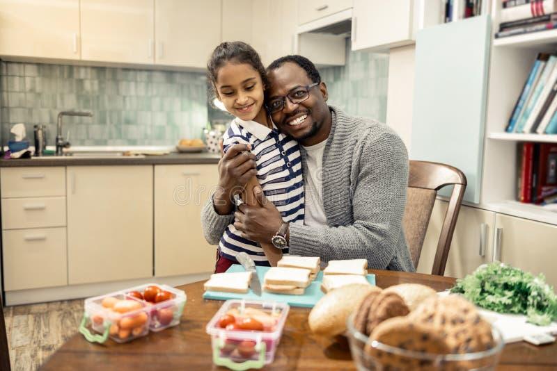 Het richten van houdende van vader die zijn leuke kleine dochter koesteren stock foto