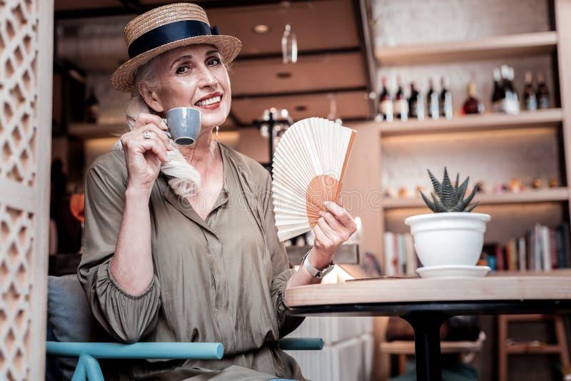 Het richten van langharige vrouw die warme dag in een koffie doorbrengen royalty-vrije stock afbeelding