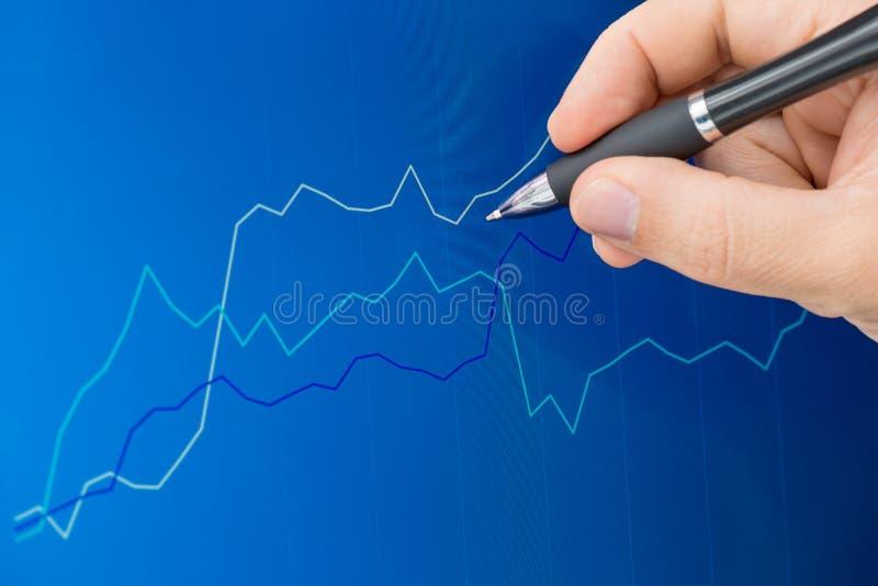 Het richten van pen op het grafiekscherm stock fotografie