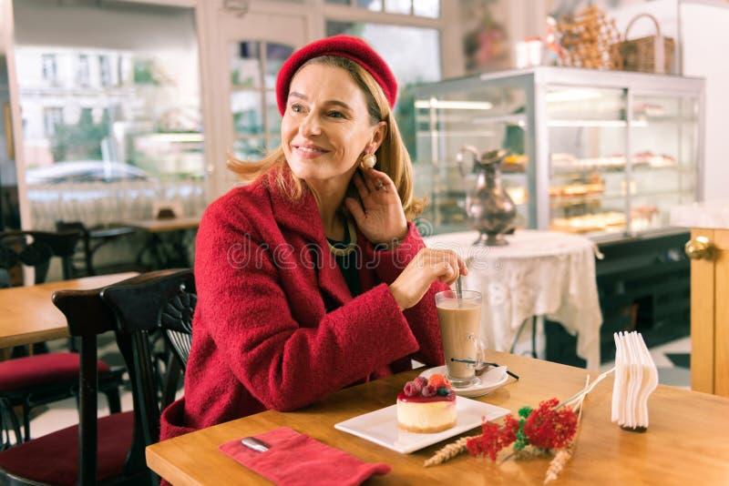 Het richten van het rijpe vrouw drinken latte en het eten van dessert in comfortabele bakkerij royalty-vrije stock foto