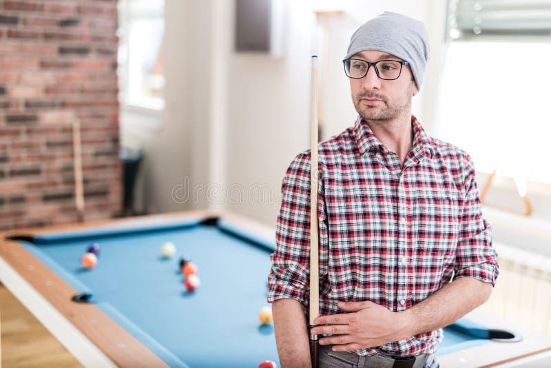 Het richtsnoer van de de holdingspool van de Hipsterkerel De lijst van de biljartsnooker op de achtergrond royalty-vrije stock foto