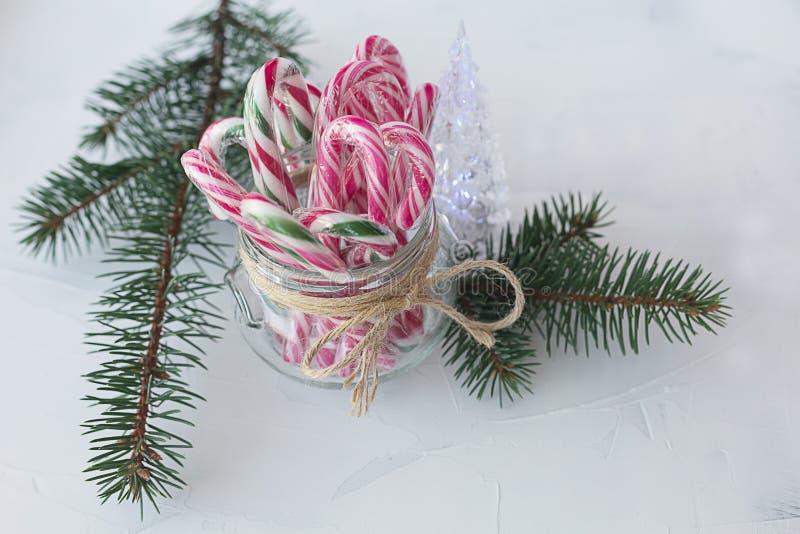 Het riet van het Kerstmissuikergoed in de takken van de glaskruik van sparren op witte achtergrond stock afbeelding