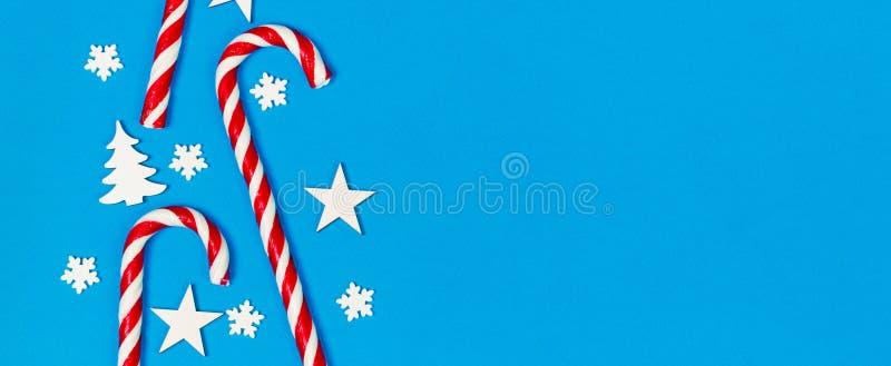Het riet van het Kerstmissuikergoed loog gelijk in rij op blauwe achtergrond met decoratieve sneeuwvlok en ster Vlak leg en hoogs royalty-vrije stock afbeeldingen