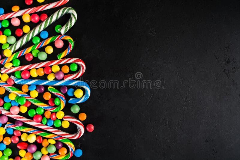 Het riet van het Kerstmissuikergoed met suikergoeddalingen over zwarte achtergrond met stock fotografie