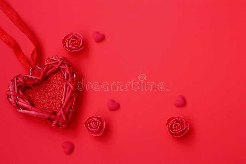Het rieten hart van Valentine, op lint, rozen op rode achtergrond royalty-vrije stock afbeeldingen