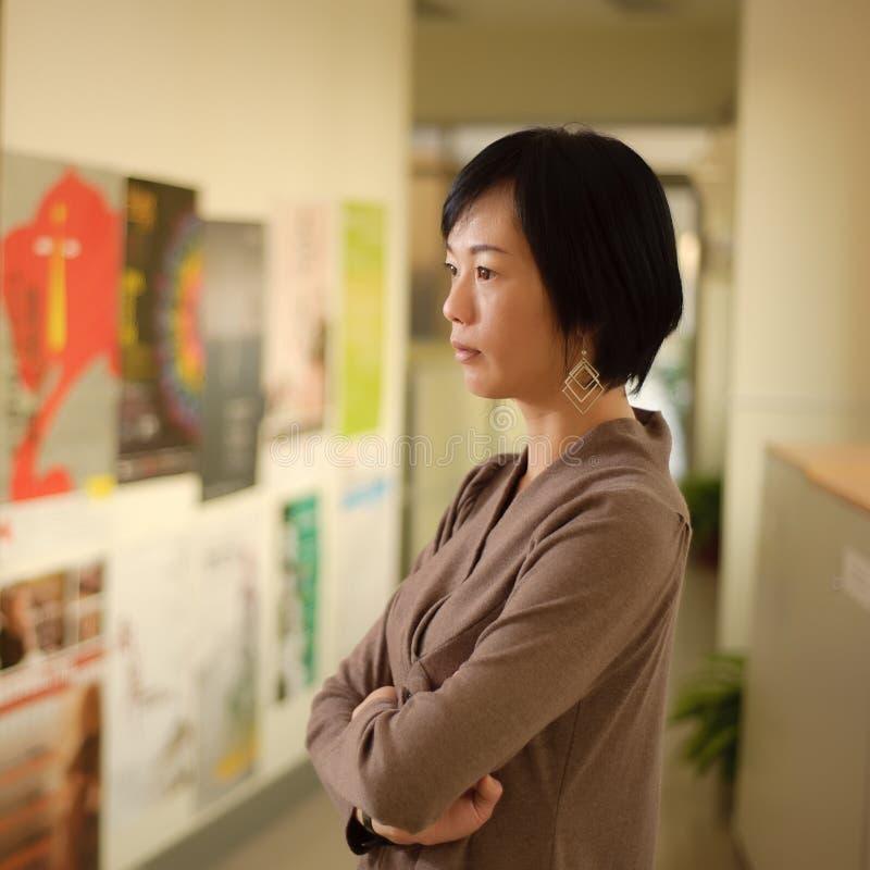 Het rijpe Aziatische vrouw denken stock foto