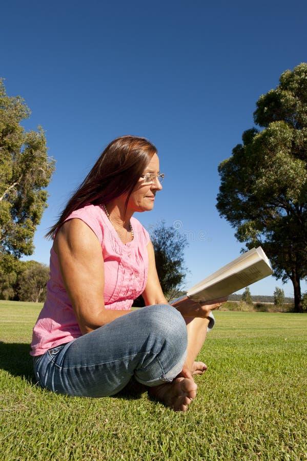 Het rijpe boek van de vrouwenlezing in park stock foto's