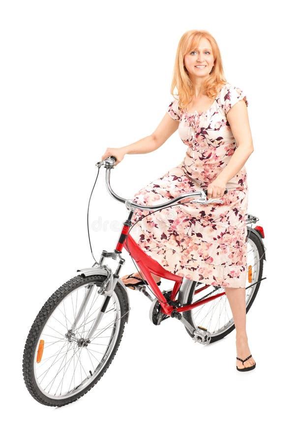 Het rijpe dame stellen gezet op een fiets stock afbeeldingen