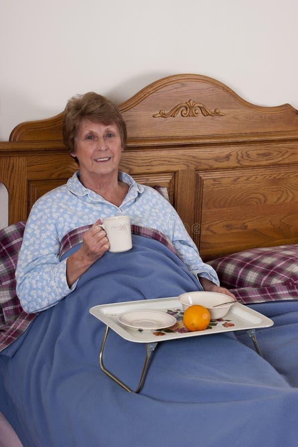 Het rijpe Hogere Ontbijt van de Vrouw in het Glimlachen van het Bed royalty-vrije stock foto's