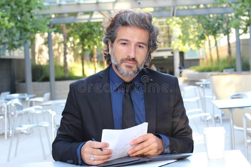 Het rijpe mensendagdromen buiten de bureauzitting op in openlucht dient met een document in zijn handen in omhoog starend in verl royalty-vrije stock foto's