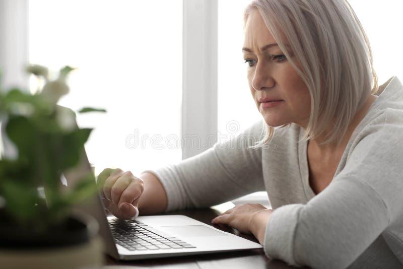 Het rijpe nieuws van de vrouwenlezing op laptop het scherm in koffie stock foto
