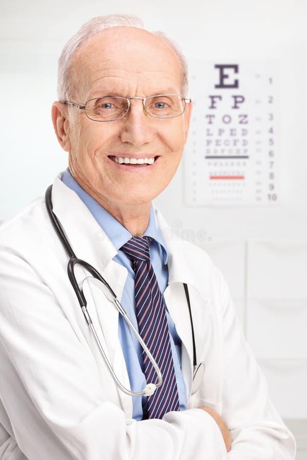Het rijpe opticien stellen in zijn bureau royalty-vrije stock afbeelding