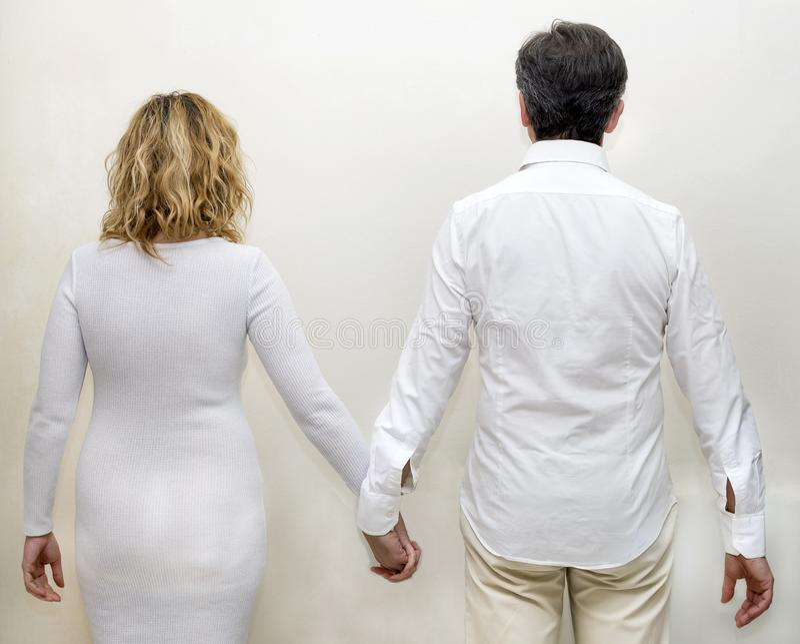 Het rijpe paar kleedde zich in wit van achter holdingshanden tegen een witte achtergrond stock afbeelding
