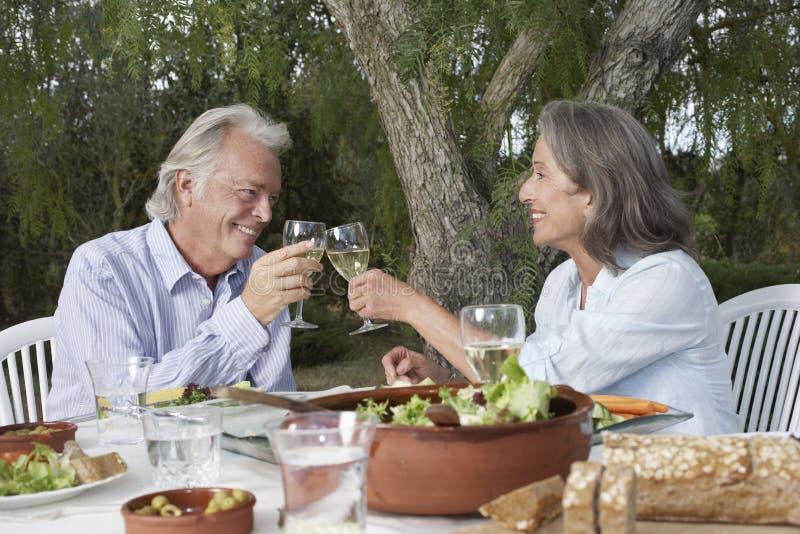 Het rijpe Paar Roosteren bij Tuinlijst stock foto