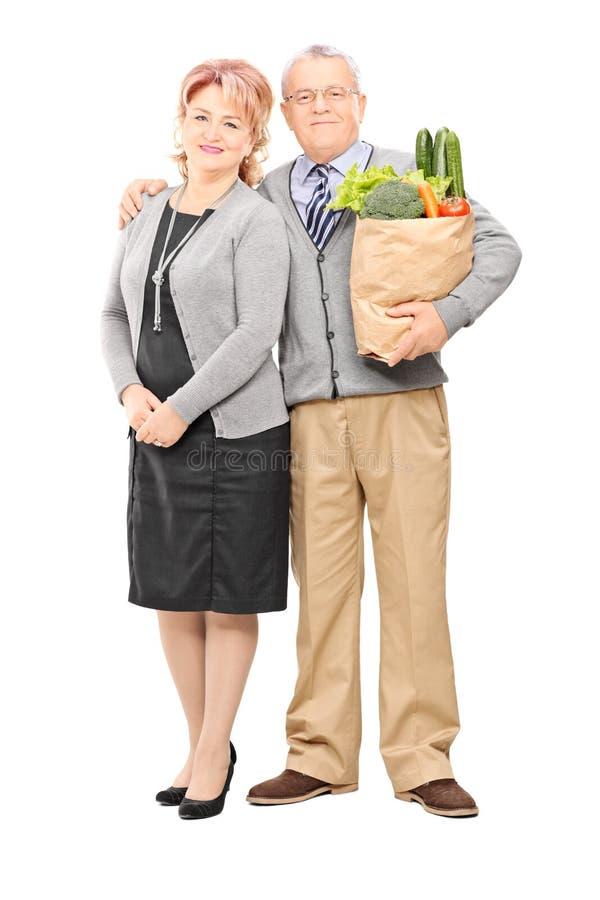 Het rijpe paar stellen met een zak van kruidenierswinkels stock fotografie