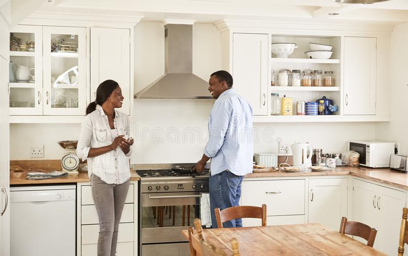 Het rijpe Paarpraatje in Keuken als Echtgenoot bereidt Ontbijt voor royalty-vrije stock foto's