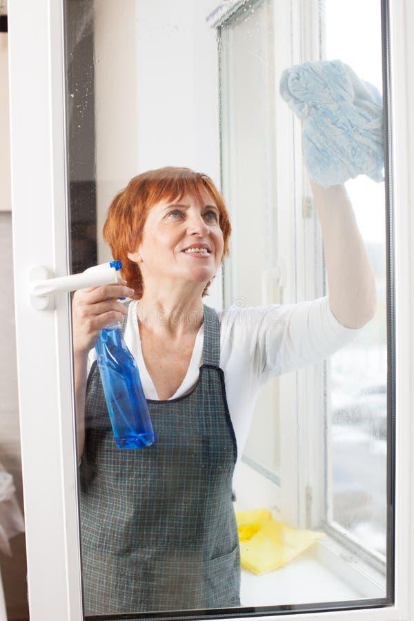 Het rijpe schoonmakende venster van het vrouwen schoonmakende venster royalty-vrije stock fotografie
