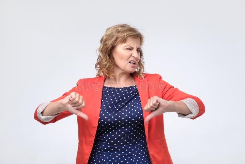 Het rijpe vrouw geven negatieve duimen onderaan gebaar van afkeuring stock foto