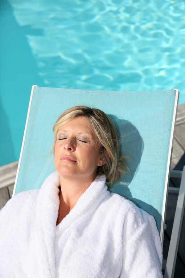 Het rijpe vrouw ontspannen door het zwembad royalty-vrije stock fotografie