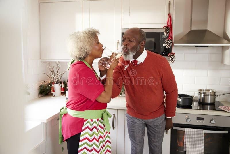 Het rijpe zwarte paar vieren op Kerstmisdag die een toost met wapens drinken strengelde, selectieve nadruk ineen royalty-vrije stock foto
