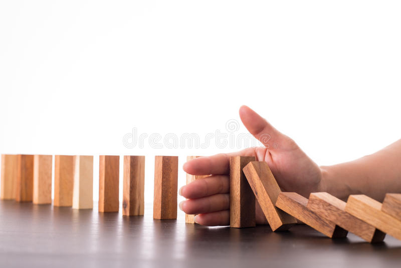Het risicoeffect van de eindedomino, zakenman die hand voor beheer s gebruiken stock afbeelding