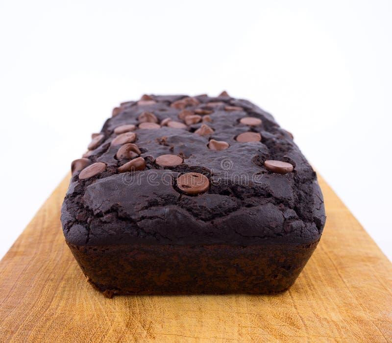 Het rode brood van de boonbrownie met chocoladeschilfers op houten scherpe raad stock afbeelding