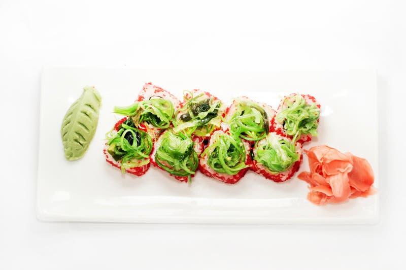 Het rode broodje van tobikosushi platted op een witte plaat stock fotografie