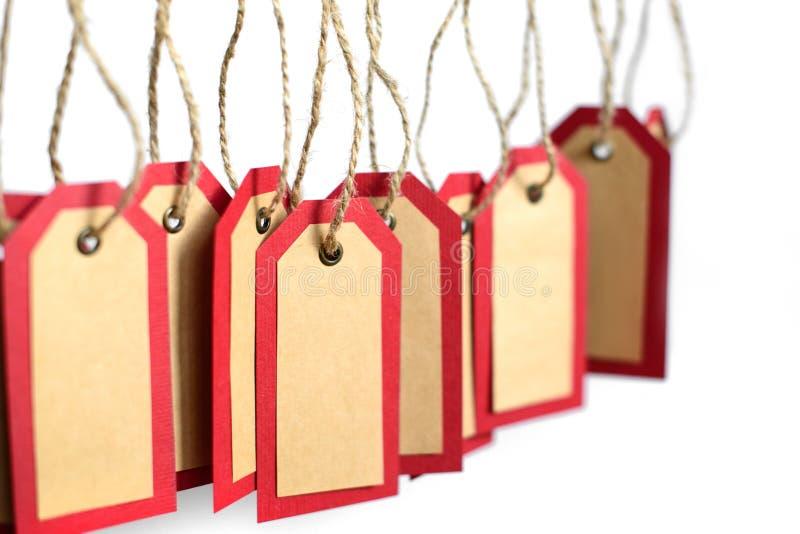 Het rode die en pakpapier etiketteert het hangen op de kabel met exemplaarruimte op witte achtergrond wordt geïsoleerd royalty-vrije stock foto's