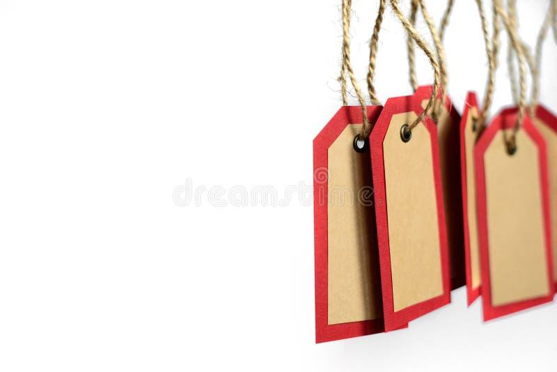 Het rode die en pakpapier etiketteert het hangen op de kabel met exemplaarruimte op witte achtergrond wordt geïsoleerd stock afbeelding