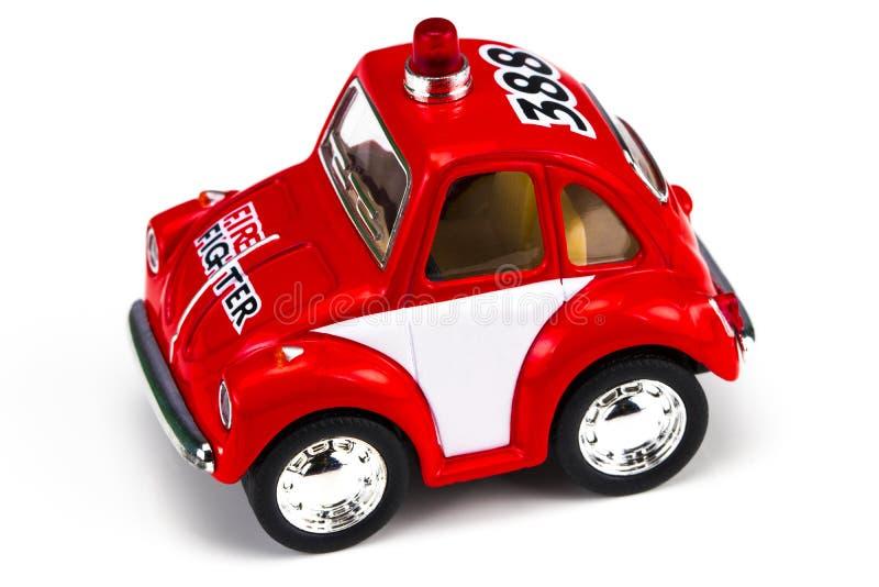 Het rode die stuk speelgoed van de brandmotor over een witte achtergrond wordt geïsoleerd stock afbeelding