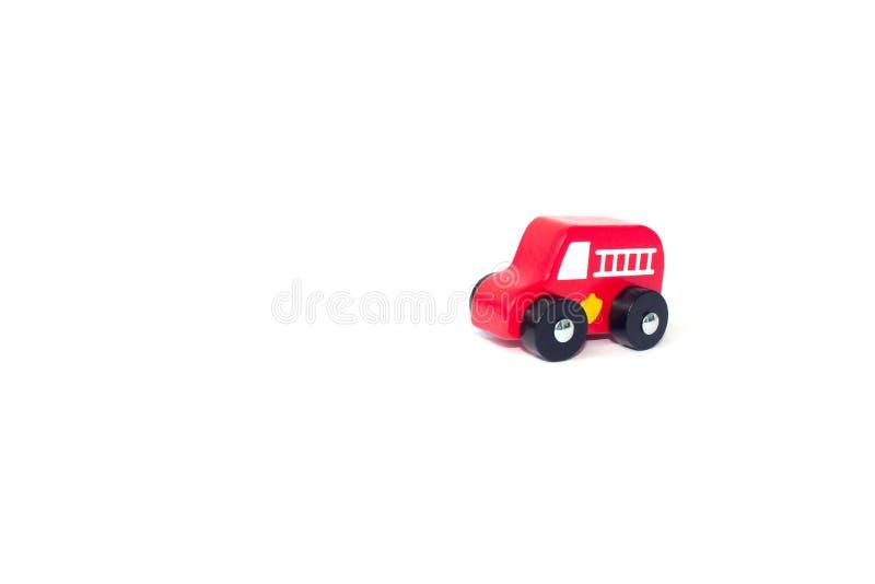 Het rode die stuk speelgoed van de brandmotor over een witte achtergrond wordt geïsoleerd stock foto