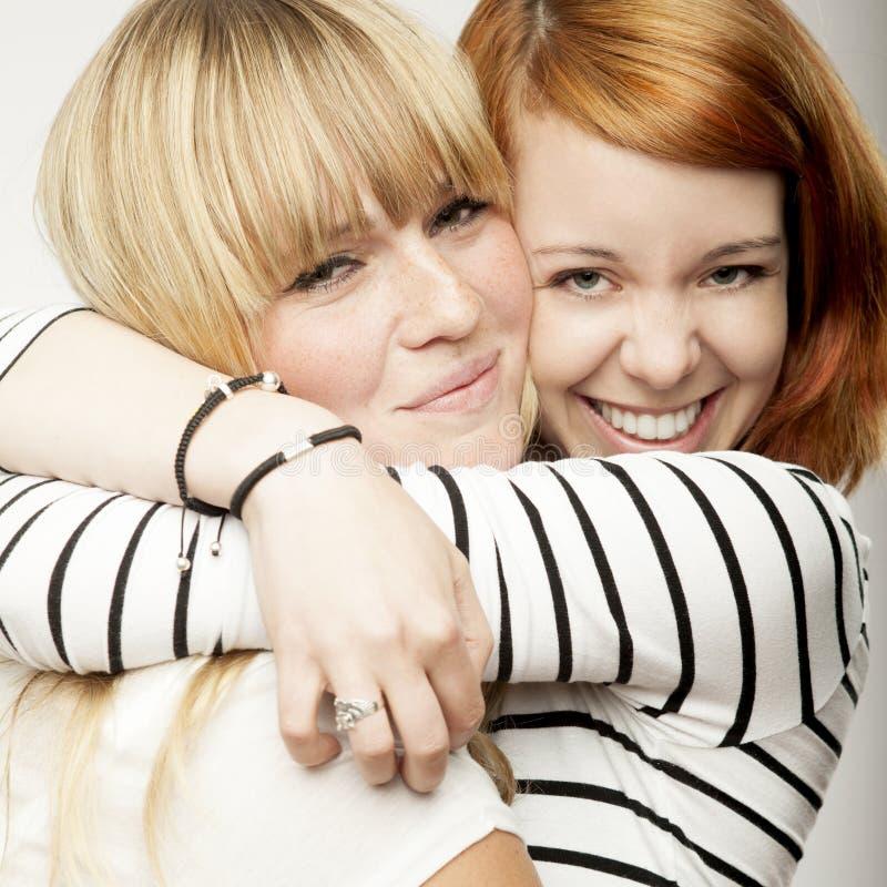Het rode en blonde haired meisjes lachen en omhelzing royalty-vrije stock foto