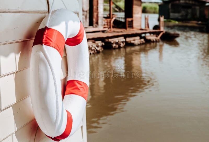 Het rode en witte reddingsboeitorus hangen op houten muur van rivierfl royalty-vrije stock foto