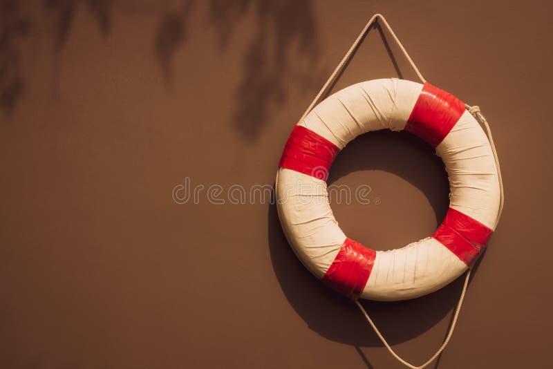 Het rode en witte van de veiligheidstorus of reddingsboei hangen op bruine muur stock fotografie