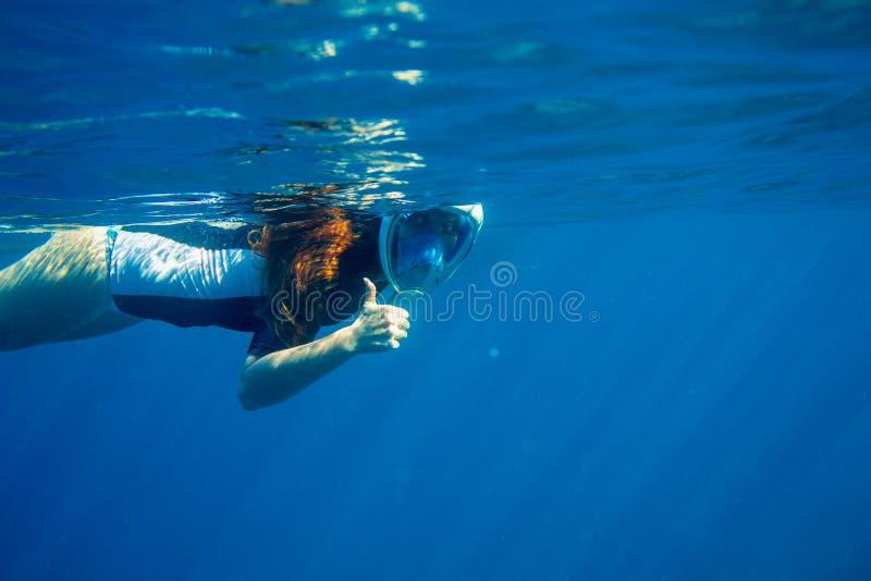 Het rode haarvrouw onderzees snorkelen Snorkel tonen duim omhoog onderwater Onderwaterfoto van vrouw het snorkelen stock foto