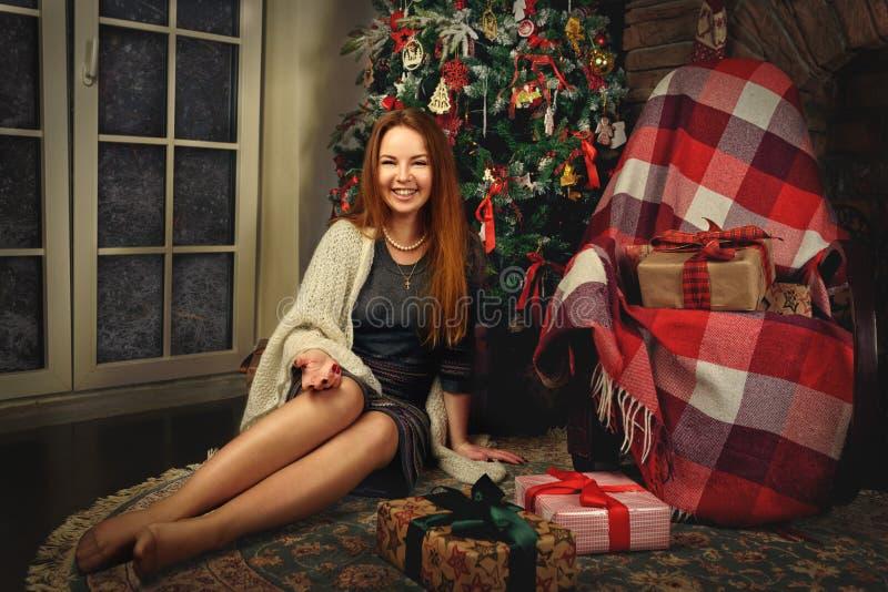 Het rode haarvrouw stellen in studio met Kerstmisdecoratie stock afbeelding