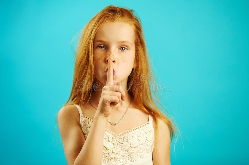 Het rode haired meisje met strikte blik zet haar vinger aan lippen, aantoont geheim en de vertrouwelijkheid, vertelt niet iederee stock fotografie