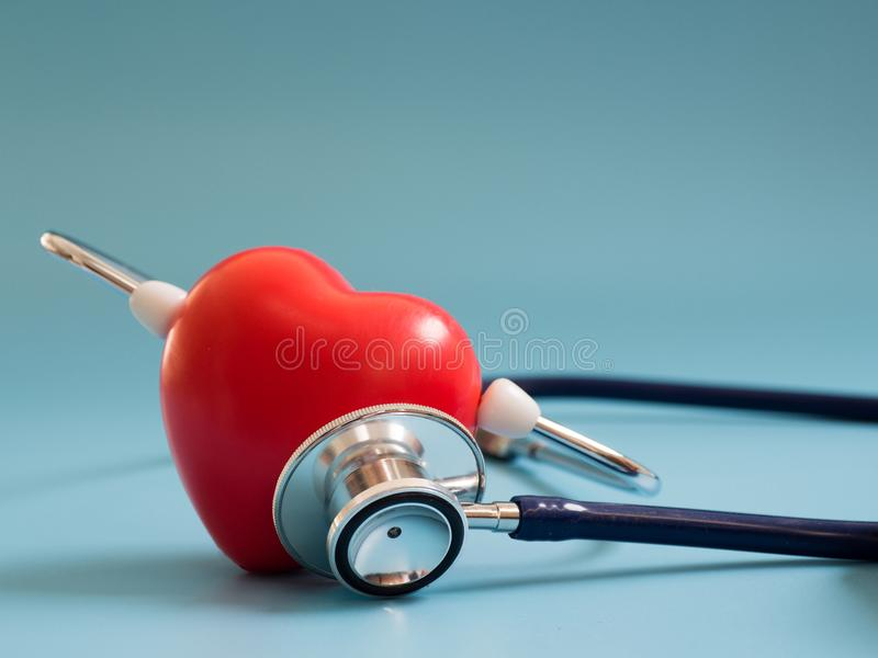 Het rode hart die diepe blauwe stethoscoop op de blauwe achtergrond met behulp van voor hoort hun eigen hart Concept liefde en ge stock afbeeldingen