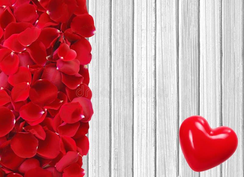 Het rode hart en nam bloemblaadjes op witte houten achtergrond toe royalty-vrije stock afbeeldingen