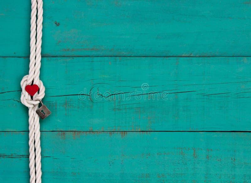 Het rode hart en slot hangen op witte kabelgrens tegen blauwe achtergrond stock afbeelding