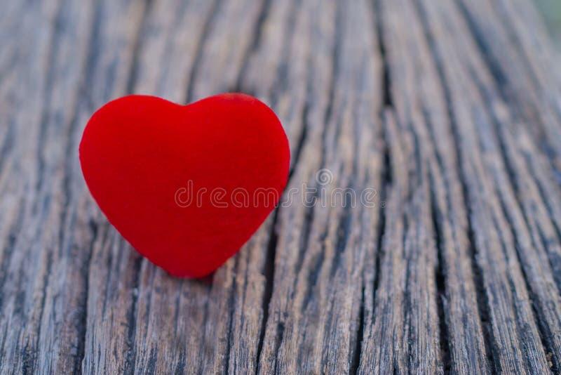Het rode hart wordt geplaatst op de houten vloer en heeft exemplaarruimte voor ontwerp in uw werk Het rode hart vertegenwoordigt  stock afbeeldingen