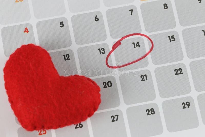 Het rode hart wordt geplaatst op de kalender en concentreert zich in Veertiende dag stock foto