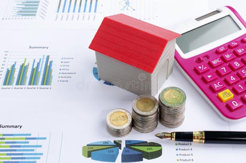 Het rode huis met muntstukstapel en de pen roze calculator voor zaken financieren concept stock afbeeldingen