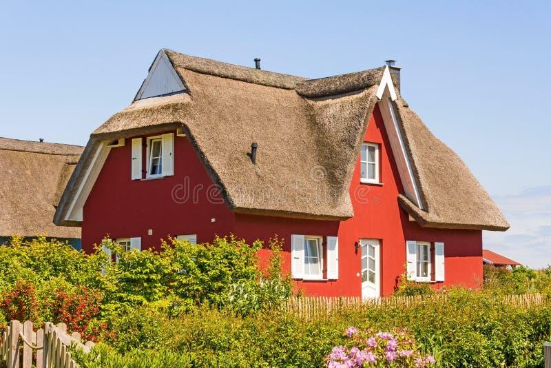 Het rode huis van de met stro bedekkenen-dakvakantie royalty-vrije stock fotografie