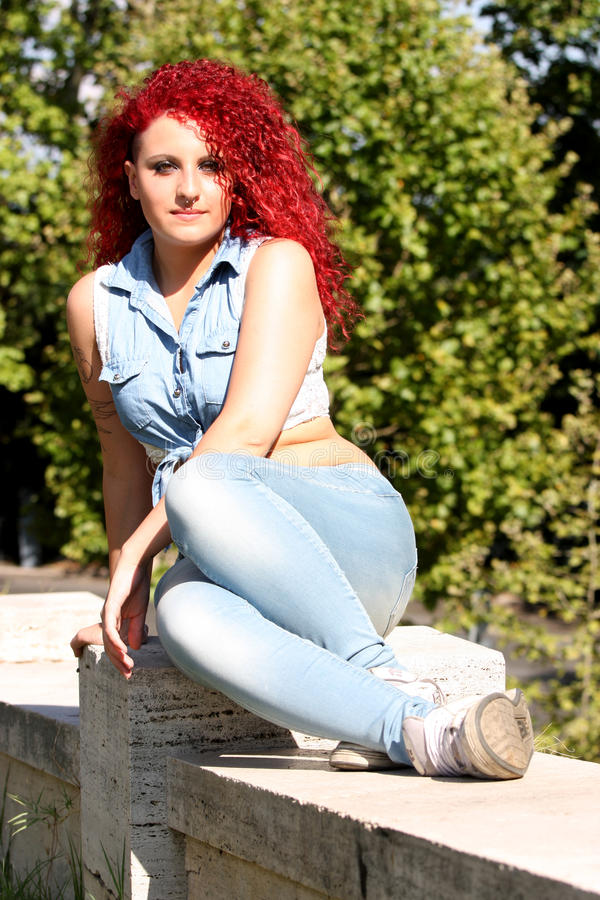 Het rode jeugdige haarmeisje kijkt openlucht stock fotografie