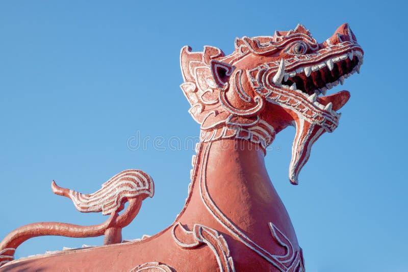 Het rode leeuwbeeldhouwwerk in de Boeddhistische tempel in Thailand royalty-vrije stock fotografie